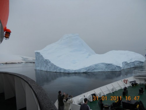 The ship passing a curvy-shaped iceberg.