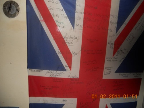 A Union Jack signed by many people, pinned to a wall, on the MV Ushuaia.