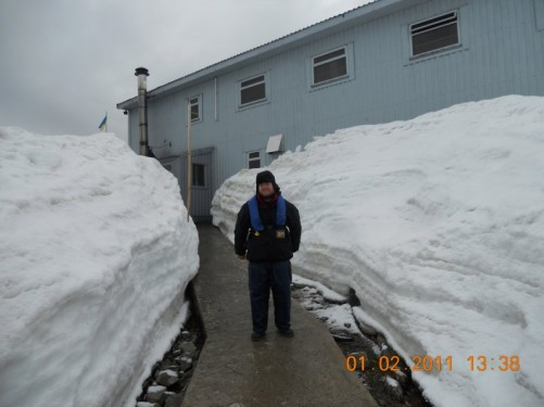 Tony standing on a path at the base. There is snow piled up higher than the top of Tony's head at either side.