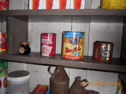 Old food containers on a shelf (Marmite, Cadbury's Drinking Chocolate, Mornflake Quick Oats). Wordie House.