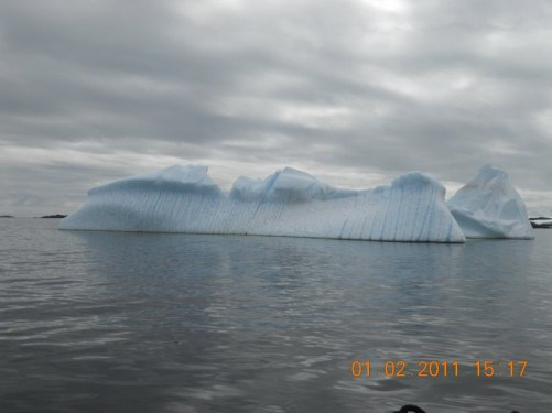 View of an iceberg with a series of blue lines running down it. Lemaire Channel.
