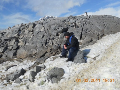 Tony resting on a rock; a pair of Gentoo penguins can be seen on the ridge of rock alongside.