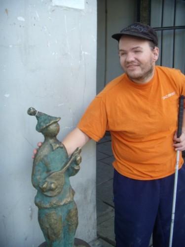 Tony touching a small bronze statue.