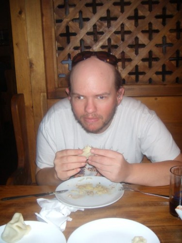 Tony eating dumpling shaped food called Khinkali in a restaurant in Tbilisi.