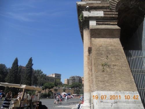 Souvenir stall and tourists alongside the Colosseum.