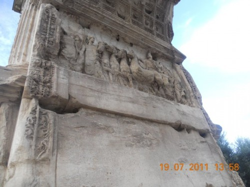 Close-up of a stone relief depicting a chariot accompanied by the Goddess Victoria and the Goddess Roma. Arch of Titus.