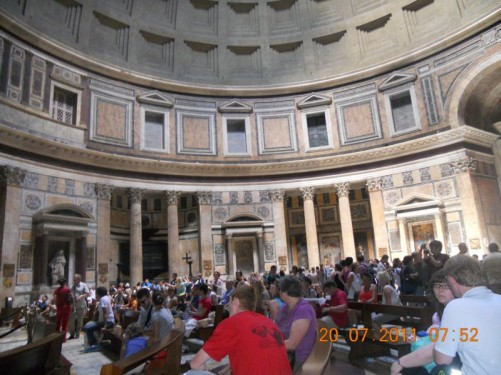 Many visitors sitting inside the Pantheon.