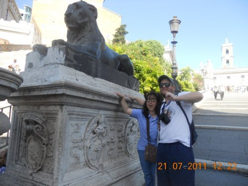 Tony, Tatiana by a lion statue at the bottom of steps leading to Piazza di Campidoglio and the Palazzo Senatorio.