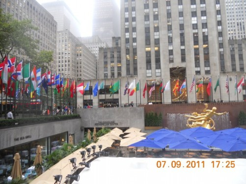 Sign: 'The Concourse, Rockefeller Center'. Public area, flags of many countries around the edge. Below a café and a fountain (partially hidden in the photo by the café's umbrellas).