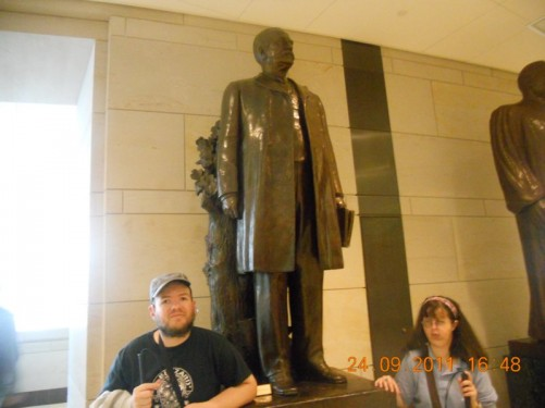 Bronze statue of a man holding a book, one of 24 statues in Emancipation Hall, Capitol Visitor Center.