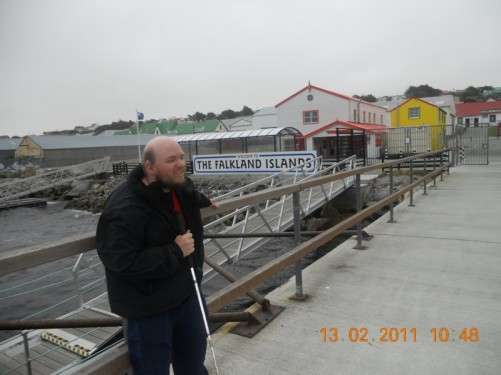 Tony standing on a jetty in Stanley Harbour. Sign reads 'Welcome to the Falkland Islands'.
