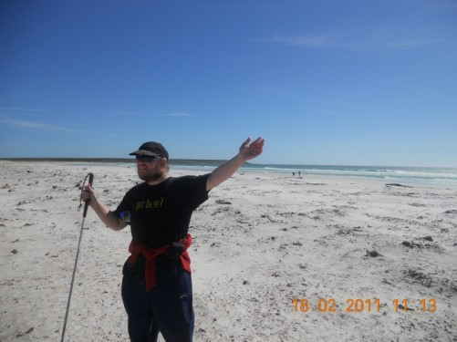 Tony stood on Volunteer Beach, the beach is approximately 2 km long, sandy and has nearby seasonal ponds, the wind blows constantly.