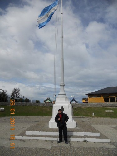 Tony in front of a large flagpole, flying the Argentine flag, on Ushuaia harbour front.