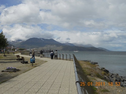 Paved walkway along the sea front by the harbour, snow covered Martial Mountains in background.