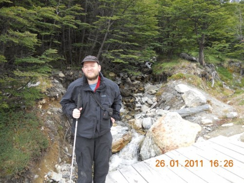 Tony standing on a wooden bridge over a glacial stream that emanates from the glacier on top of the mountain.