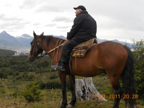 Tony on horseback, snowed-capped Martial Mountains in the distance.