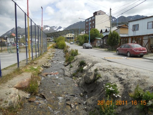 Street in Ushuaia with a small stream running down one side.