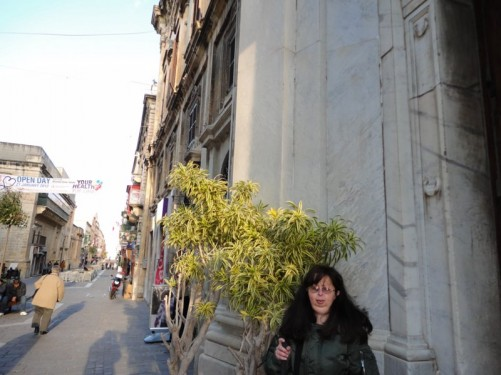 Tatiana standing at the side of Merchants Street (Triq Il-Merkanti), Valletta. A long straight street with shops and cafés. It runs parallel to Republic Street.