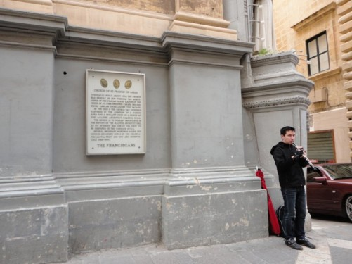 A man playing a musical instrument (probably an oboe) outside the Church of St. Francis of Assisi.