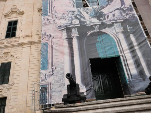 The baroque stone façade of the Auberge de Castille, partially obscured due to building work. It is now the Prime Minister's office.