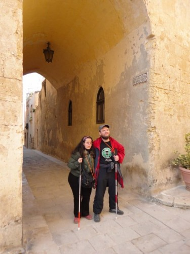 Tatiana and Tony on a narrow street: Triq Santa Sofia. They are in front of a short covered section as the street passes beneath a building.
