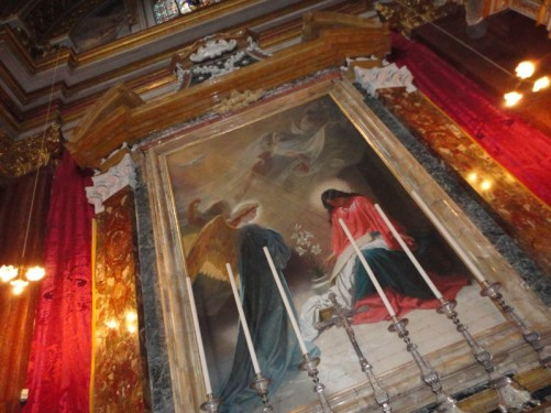 A large painting above an altar inside the cathedral.