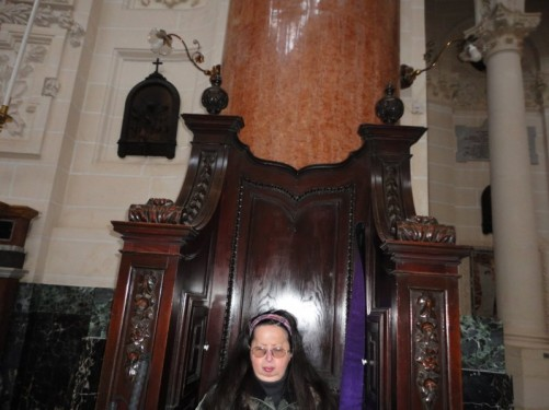 Tatiana sitting in a large wooden chair inside the Basilica of Our Lady of Mount Carmel.