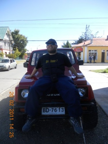 Tony sat on the front of a 4x4 car belonging to a fellow traveller from Switzerland, outside the hostel.