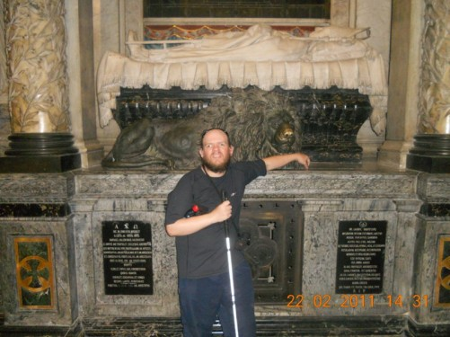 Tony in front of a large tomb decorated with a metal-cast lion. The Metropolitan Cathedral of Santiago.