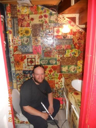 Tony inside an impressively decorated bathroom/toilet. Don Santiago Hostel.