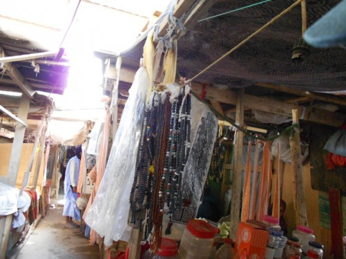 Narrow route between market stalls – cheap necklaces for sale at the nearest stall.