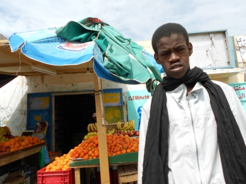In front of a fruit stall. The young African stall owner staring at the camera.
