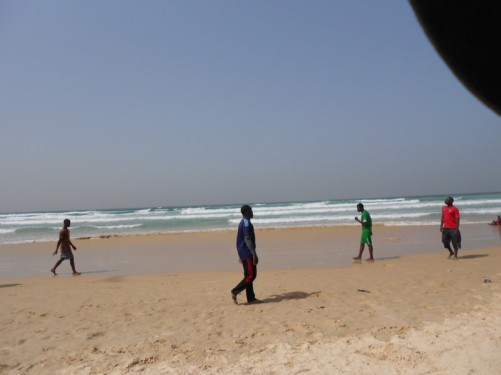 Yoff Beach. Looking towards the Atlantic Ocean. A group of local men in front, kicking a football about.