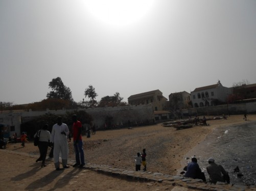 A beach by the harbour at Gorée. On the beach are a few small fishing boats. Plus, a few locals sitting by the water.