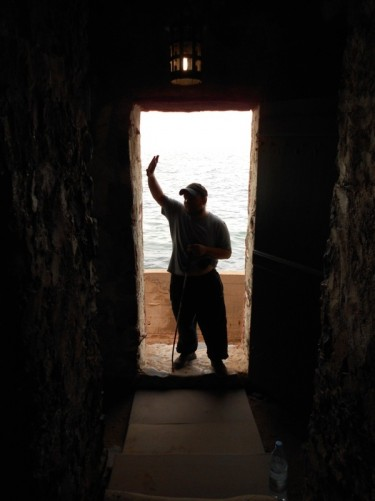 Tony standing in a doorway that looks out towards the sea. This is the 'door of no return' that slaves left through.