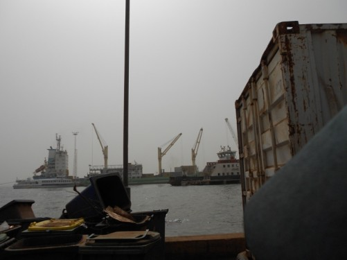 Banjul port. A shipping container in the foreground; boats and cranes in the middle distance.