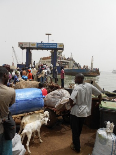 A queue of people, some with goods piled on carts, waiting to board a ferry at Banjul port. A pair of goats are tied to a cart immediately in front.