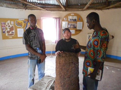 Tony, with two guides, touching a stone inside a small museum at the Wassu Stone Circles archaeological site.