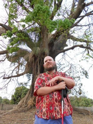 Tony in front of a large tall tree. The sacred tree – largest in Abene.