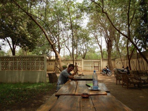 Chairs and tables outside The Sleeping Camel Guesthouse. Compound shaded by trees and surrounded by high walls.