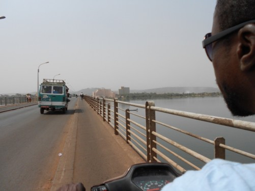 View from a motorcycle crossing Martyrs Bridge (Pont Des Martyrs) over the wide Niger River in Bamako. Heading towards the commercial and administrative centre of the city on the north side of the river. Photos taken by Tony who is on the back of the motorbike.