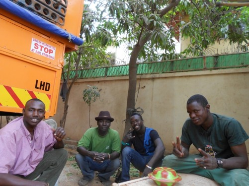 Four local guys crouching around a table. Still in the guesthouse compound. Taken outdoors, a wall behind.