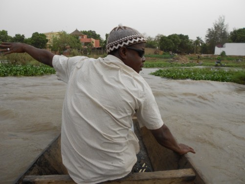 View from a canoe on a wide part of the Niger River: near the bank, which is green and lush. A local guide sitting in front of the camera.