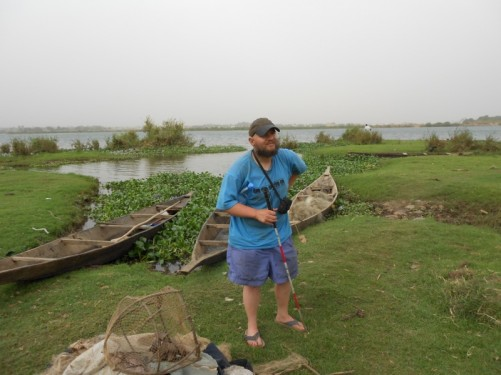 Tony on the grassy bank of the Niger River. Three canoes and a fishing net around him.