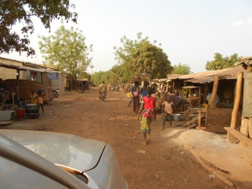 A main street through a village. Unpaved dirt road. Everyday activity occurring.