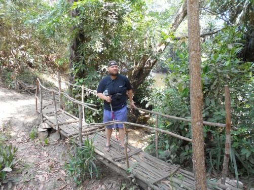 Tony standing on a narrow wooden bridge, near the waterfalls.