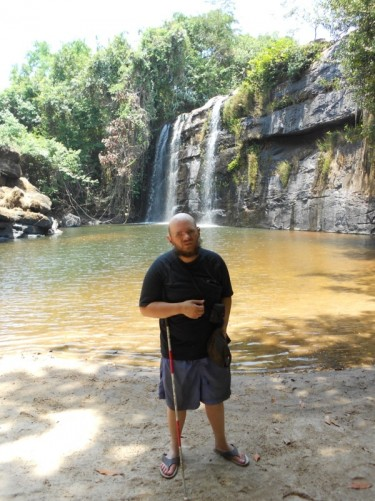 Tony in front of the waterfall. Standing on sand by the water.