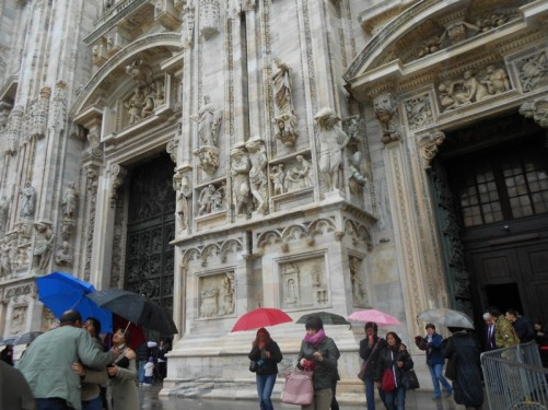 Visitors leaving the cathedral. It's raining. People with umbrellas up.