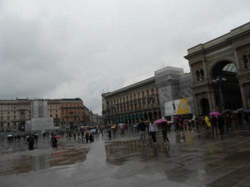 Duomo Square. It's raining. Buildings reflected on the wet paving slabs.