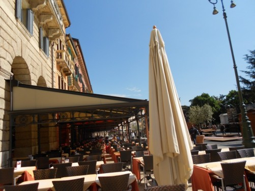 Rows of café and restaurant tables at the edge of Piazza Bra. Verona's largest square, located in the city centre.